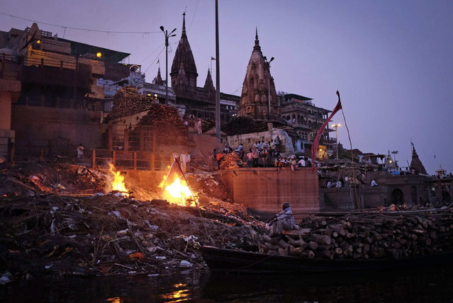 People watch as pyres burn at a cremation ground on the banks of river Ganges in Varanasi, in the northern Indian state of Uttar Pradesh, June 19, 2014. (Photo by Danish Siddiqui/Reuters)