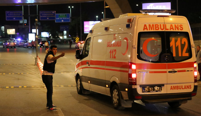 A policeman gestures in front of an ambulance at Istanbul Ataturk airport, Turkey, following a blast June 28, 2016. (Photo by Goran Tomasevic/Reuters)