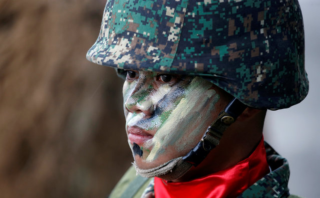 A soldier with a painted face takes part in a military parade to honor Philippine President Benigno Aquino, a few days before he leaves office for incoming President-elect Rodrigo Duterte at military's main Camp Aguinaldo in Quezon city, Metro Manila, Philippines June 27, 2016. (Photo by Erik De Castro/Reuters)