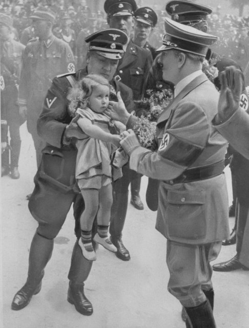 German Chancellor Adolf Hitler, right, accepts a bouquet of flowers from a young German girl on the occasion of his visit to Stettin, Germany, where he is attending a Nazi party meeting, June 21, 1938. (Photo by AP Photo)