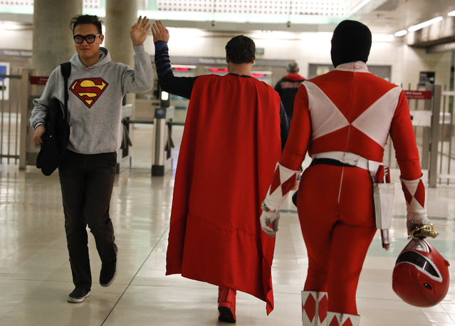 "In this Tuesday, May 16, 2017 photo, Superman impersonator Justin Harrison, center, high-fives a commuter wearing a sweatshirt with a Superman symbol printed on it as he and his roommate, Reginald Jackson, in a Red Power Ranger costume, head back home after working on Hollywood Boulevard, in Los Angeles. ""When I put on any costume of any character, I automatically feel like I am that character"". (Photo by Jae C. Hong/AP Photo)"