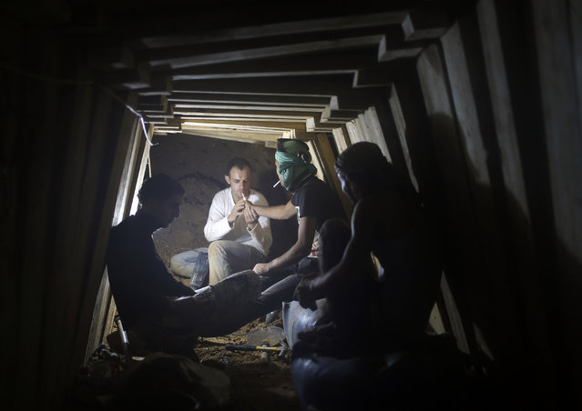 Palestinians smoke cigarettes as they work inside a smuggling tunnel dug beneath the Egyptian-Gaza border in Rafah, in the southern Gaza Strip November 26, 2012. Knee-deep in craters carved out by Israeli air strikes, Palestinians wielded shovels and planks to reopen tunnels used to smuggle in goods from Egypt to Gaza, as international aid agencies raced to replenish Gaza's supplies. (Photo by Mohammed Salem/Reuters)
