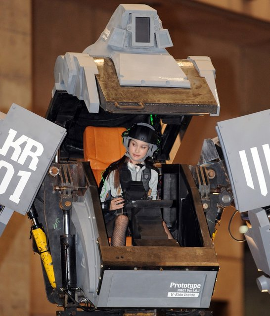 """Female """"pilot""""' Anna (C) looks out the cockpit of Japanese electronics company Suidobashi Heavy Industry's newly unveiled robot """"Kuratas"""" at the Wonder Festival in Chiba, suburban Tokyo on July 29, 2012. The Kuratas robot, which will go on sale with a price tag of one million USD, measures four meters in height, weighs four tons and has four wheeled legs that can either be controlled remotely through the 3G network or by a human seated within the cockpit."""