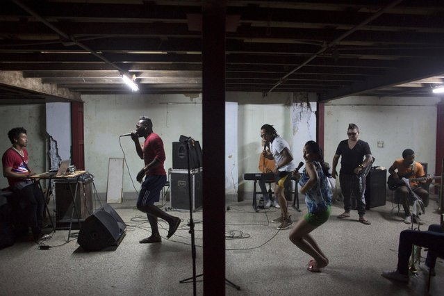 "Singers Raciel Lopez, 30 (center, L), and Maria Despaigne (center, R), perform during a rehearsal of the band ""Carlon y La Novena"" in downtown Havana, February 10, 2015. (Photo by Alexandre Meneghini/Reuters)"