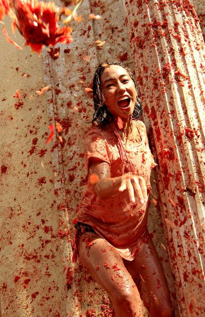 """People take part in the traditional """"Tomatina"""" or tomato battle in Bunol, Spain, on 26 August 2015. Crowds throw tons of ripe tomatoes at each other and are soaked with smashed tomatoes and juice in just a few minutes. The worldwide known festival, that has charged an entrance fee during the past three years to limit it's capacity, attracts numerous foreign youths to join in the funny tomato-fight. (Photo by Alberto Saiz/AP Photo/SIPA Press)"""