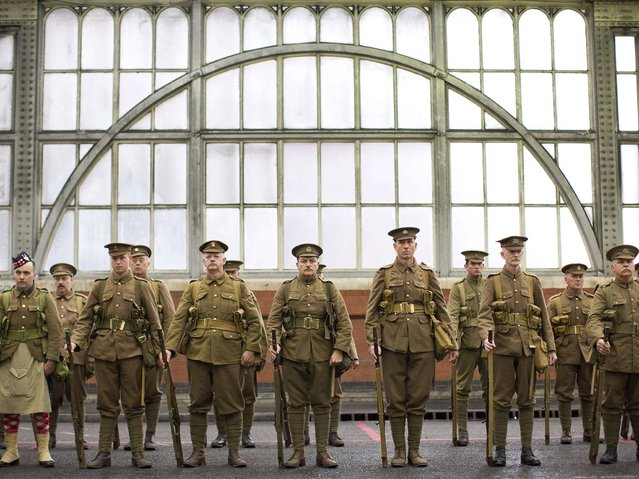 Members of the Association of Military Remembrance, also known as The Khaki Chums, stand in ranks as they re-enact the journey 100 years ago today of the first WW1 soldiers to mobile at London's railway stations to travel to the south coast before onward deployment to France at Waterloo station in London on August 10, 2014. (Photo by Justin Tallis/AFP Photo)