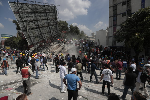 Rescue workers and volunteers search a building that collapsed after an earthquake in the Roma neighborhood of Mexico City, Tuesday, September 19, 2017. (Photo by Eduardo Verdugo/AP Photo)