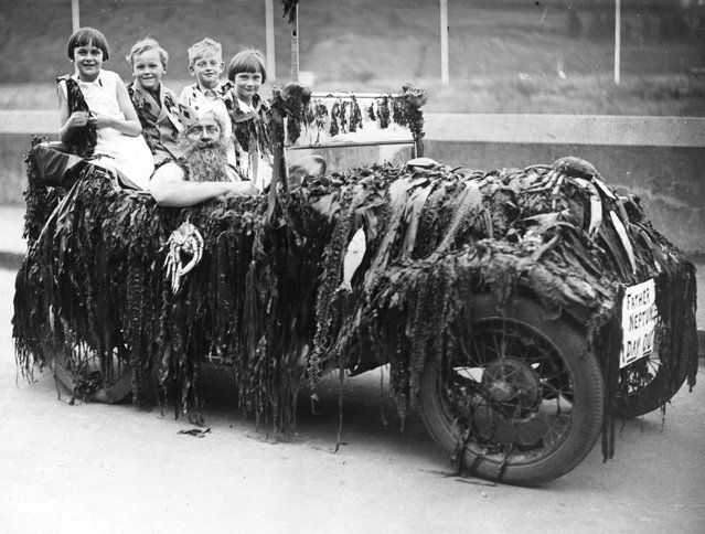 Children sitting in the back of an Austin Seven car driven by a man dressed as King Neptune, in the procession to celebrate the opening of Dartmouth's Carnival Week. 13th July 1936.