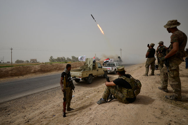Shi'ite Popular Mobilization Forces (PMF) with Iraqi rapid response members fire a missile against Islamic State militants on the outskirts of Shirqat, near Kirkuk, Iraq September 23, 2017. (Photo by Reuters/Stringer)