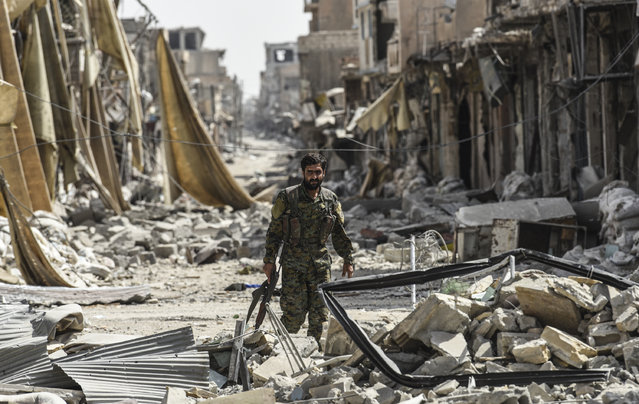 A member of the Syrian Democratic Forces (SDF) walks through the debris in the old city centre on the eastern frontline of Raqa on September 25, 2017. Syrian fighters, backed by US special forces, are battling to clear the last remaining Islamic State (IS) group fighters holed up in their crumbling stronghold of Raqa. (Photo by Bulent Kilic/AFP Photo)