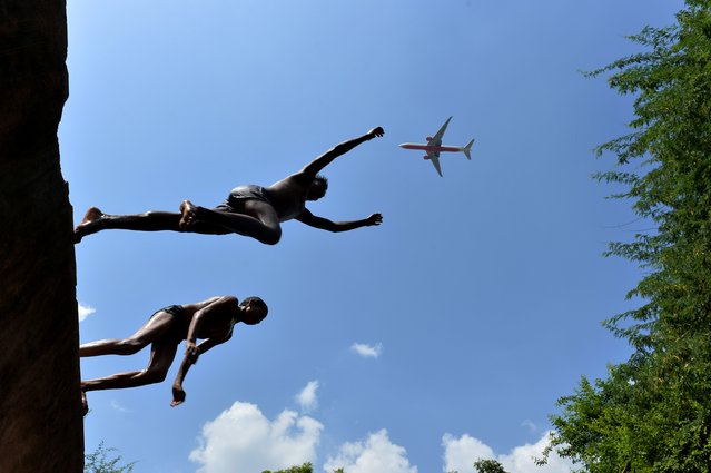 """A plane flies overhead as Indian youth jump into the water at the Gandak ki Baoli, """"a well with steps"""" which was constructed during the rule of Emperor Iltutmish who was also the founder of the slave dynasty, in New Delhi on August 26, 2014. Emperor Iltutmish founded the Delhi Sultanate and ruled from 1211. (Photo by Chandan Khanna/AFP Photo)"""