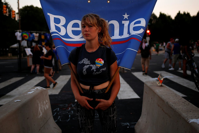 A woman on roller skates carries a flag supporting U.S. Senator Bernie Sanders along the perimeter walls of the 2016 Democratic National Convention in Philadelphia, Pennsylvania on July 27, 2016. (Photo by Adrees Latif/Reuters)