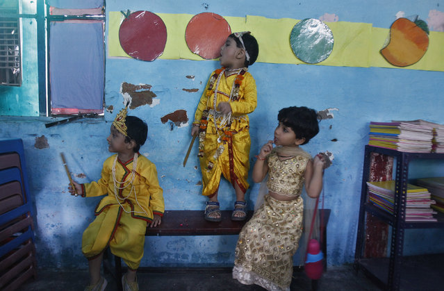 Boys dressed as Lord Krishna and a schoolgirl (R) wait for their performance to start inside a classroom during the celebrations to mark Janmashtami festival in New Delhi August 27, 2013. (Photo by Anindito Mukherjee/Reuters)