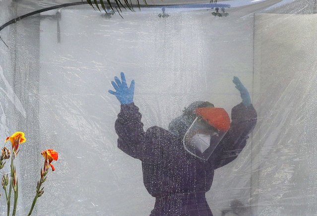 A health worker wearing a protective suit is disinfected inside a portable tent outisee the Gat Andres Bonifacio Memorial Medical Center during an enhanced community quarantine to prevent the spread of the new coronavirus in Manila, Philippines, Monday April 27, 2020. (Photo by Aaron Favila/AP Photo)