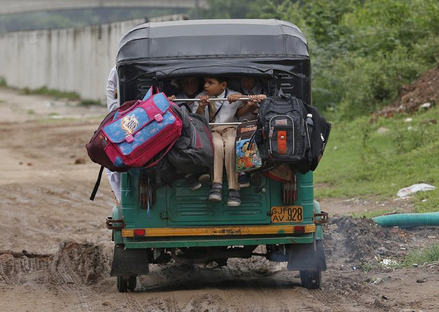School children travel on a packed auto-rickshaw on their way to school in the western Indian city of Ahmedabad September 5, 2014. (Photo by Amit Dave/Reuters)
