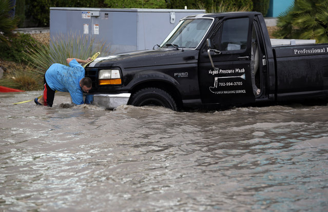 A man hooks up a tow line to his stalled truck in a flooded street Monday, September 8, 2014, in Las Vegas. Heavy rains in the Las Vegas valley caused flooding on city streets. (Photo by John Locher/AP Photo)