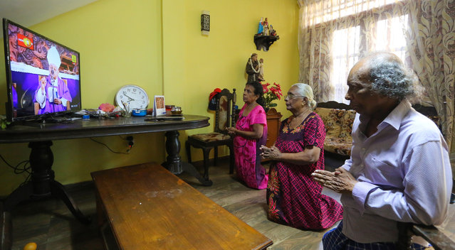 A Sri Lankan Catholic family observe the Sunday mass at home in Colombo, Sri Lanka, 15 March 2020. Sri Lankan government closed schools and Colleges, Universities, cinema halls, and have cancelled all other mass gathering events across the country in order to prevent the spread of the coronavirus SARS-CoV-2 which causes the Covid-19 disease. Sri Lankan health ministry on 14 March said five new case was diagnosed with coronavirus in the country, bringing to ten the total number of confirmed cases in Sri Lanka. (Photo by Chamila Karunarathne/EPA/EFE)