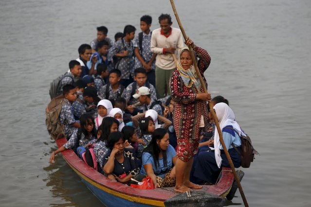 Students sit in a wooden boat as they head home from school earlier than usual, due to the unhealthy quality of air in Palembang, on Indonesia's Sumatra island, September 10, 2015. (Photo by Reuters/Beawiharta)