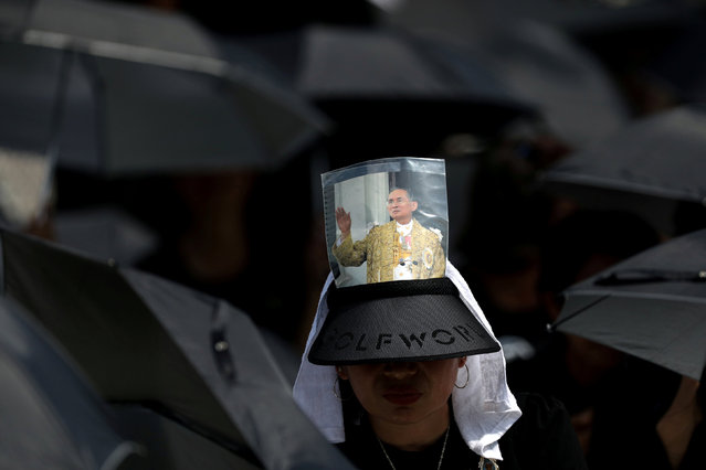 A mourner prays in a sea of black umbrellas at the funeral procession and royal cremation ceremony of late Thai King Bhumibol Adulyadej, seen on photograph, in Bangkok, Thailand, Thursday, Oct. 26, 2017. Bhumibol's death at age 88 after a reign of seven decades sparked a national outpouring of grief and a year of mourning, culminating in an elaborate funeral and cremation ceremony this week. (Photo by Athit Perawongmetha/Reuters)