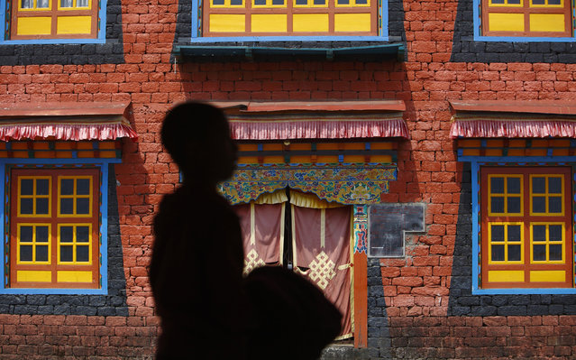 A novice monk walks past the Kyamgon Tashi Chocling Monastery at Lukla, in Solukhumbu district April 25, 2014. (Photo by Navesh Chitrakar/Reuters)