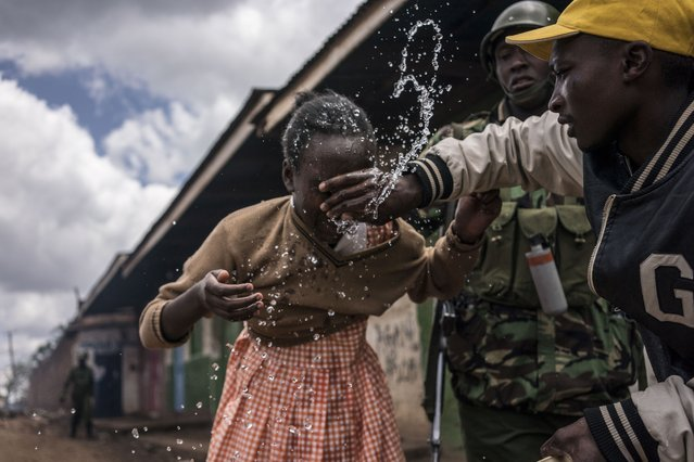 Policemen and residents help a young schoolgirl that inhaled tear gas as the police was trying to hold off a group of supporters of opposition leader while protesting in Kawangware on October 30, 2017 in Nairobi. Kenya's election board said it would announce today the winner of a highly contentious election, sparking fears of further violence in flashpoint opposition strongholds. (Photo by Fredrik Lerneryd/AFP Photo)