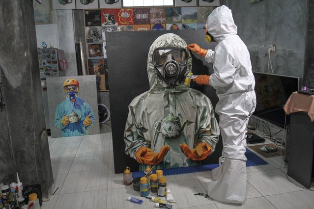 An artist wearing a protective suit paints a picture of a health worker as an appreciation for the service amid the coronavirus disease (COVID-19) outbreak in Sleman, Yogyakarta Province, Indonesia, June 5, 2020. (Photo by Hendra Nurdiyansyah/Antara Foto via Reuters)