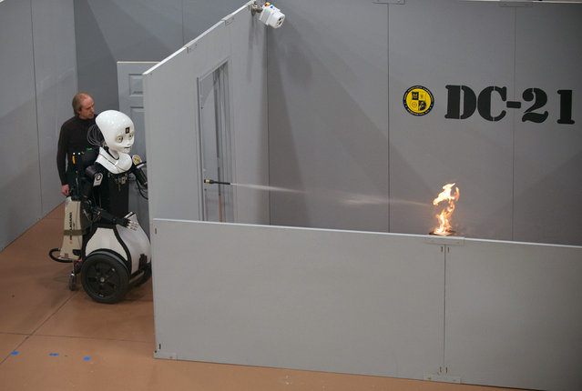 Octavia, a mobile, dexterous, social (MDS) robot, puts out a fire in the prototyping high bay of the just-opened Laboratory for Autonomous Systems Research at the Naval Research Laboratory in Washington, D.C. The LASR facility will integrate science and technology components into research prototype systems and will become the nerve center for basic research that supports autonomous systems research for the Navy and Marine Corps. (Photo by John Williams/U.S. Navy)