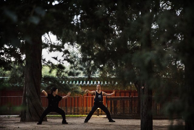 A Chinese couple practice martial arts at a park on September 17, 2014 in Beijing, China. (Photo by Kevin Frayer/Getty Images)