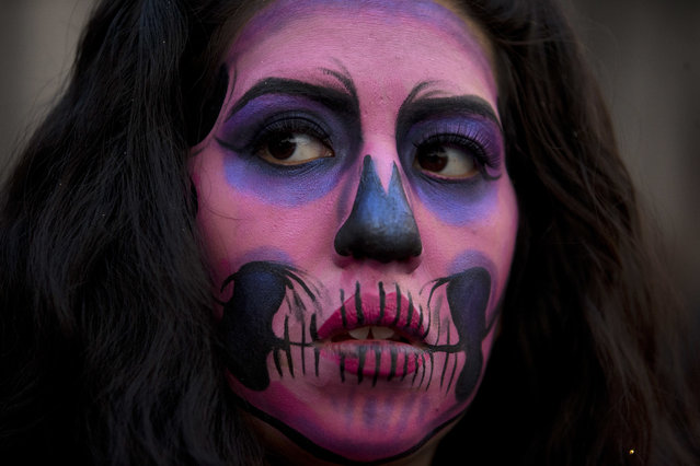 A woman with her face painted like a Catrina, participates in a Day of the Dead march calling for justice for victims of femicide, women murdered where the motive was directly related to their gender, in Mexico City, Wednesday, November 1, 2017. (Photo by Rebecca Blackwell/AP Photo)