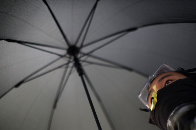 A protester holds an umbrella as he gathers around the Golden Bauhinia Square before an official flag raising ceremony to commemorate the Chinese National Day in Hong Kong, October 1, 2014. (Photo by Carlos Barria/Reuters)