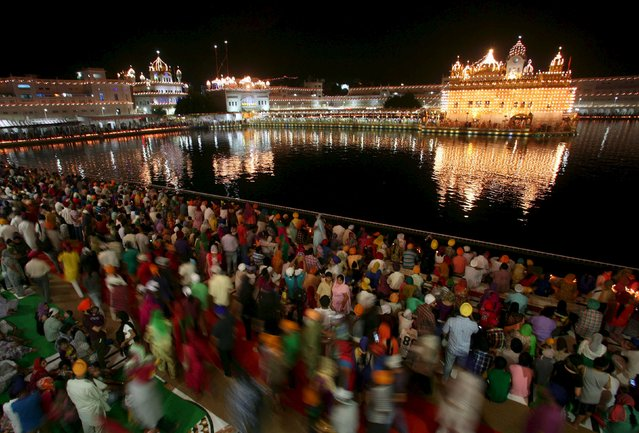 The Golden Temple is seen illuminated as Sikh devotees throng the shrine on the 411st anniversary of the installation of the Guru Granth Sahib, the religious book of Sikhs, in Amritsar, India, September 14, 2015. (Photo by Munish Sharma/Reuters)