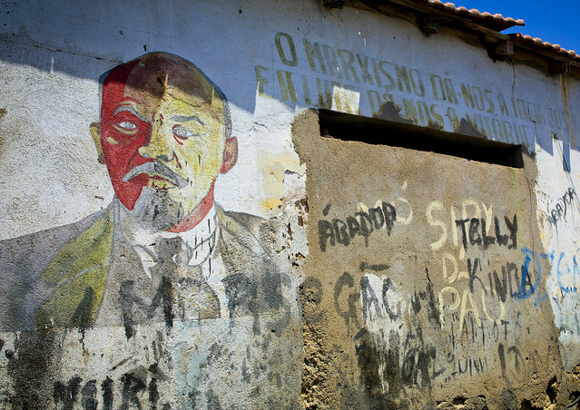"""Lenin portrait in Namibe – Angola. In Namibe, in an old garage, i saw this painted walls, with 70's communist slogans and the portrait of Lenine. Very few can still be seen i Angola. At this time, Cuba and USSR were supporting MPLA to fight UNITA party , supported by USA and South Africa"". (Eric Lafforgue)"