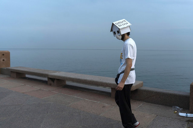 """A man wearing a face mask against the spread of new coronavirus and a cardboard house in his head with text that reads in Spanish """"Stay home"""", walks on the seafront in Montevideo, Uruguay, Wednesday, May 20, 2020. (Photo by Matilde Campodonico/AP Photo)"""