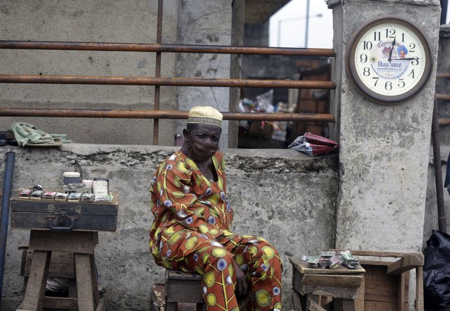 A watch repairer, wearing a face mask to protect himself from coronavirus, waits for customers on the street in Lagos Nigeria, Monday May 4, 2020. Though Nigeria begun a phased easing of its strict lockdown measures on Monday, its confirmed cases of coronavirus continue to increase. (Photo by Sunday Alamba/AP Photo)