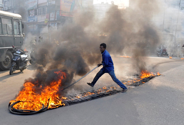 A demonstrator drags burning tires during a day-long strike to protest against the killing of Sudip Datta Bhowmik, a local journalist, who according to local media was shot dead by a Tripura State Rifles trooper on Tuesday, in Agartala, India on November 23, 2017. (Photo by Jayanta Dey/Reuters)