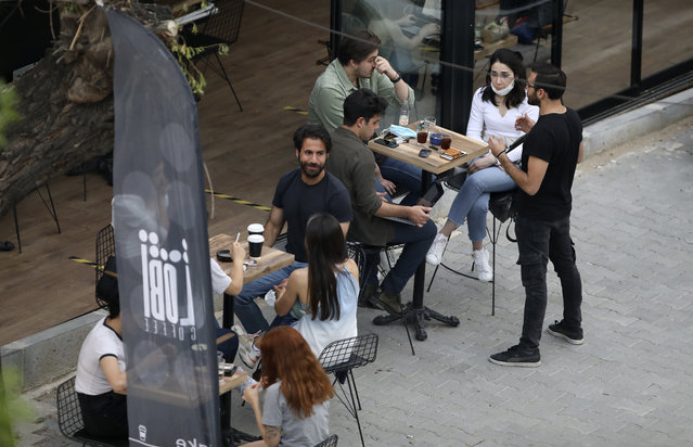 In this photo taken Saturday, June 6, 2020, people sit outside a cafe, in Ankara, Turkey.  Images on social media and news agencies showed crowds picnicking and partying Saturday night without heeding to the rules of social distancing and wearing masks on the first weekend with no lockdown, prompting a reprimand from the health minister who warned that the novel coronavirus continued to pose a threat. (Photo by Burhan Ozbilici/AP Photo)