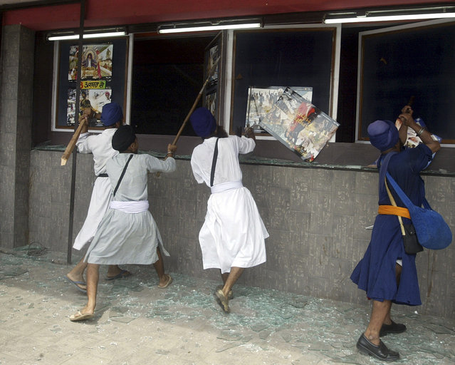 """Activists from Youth Federation Bhindranwale, a radical Sikh organization, break display windows of a cinema house during their protest against the Bollywood movie """"Singh is Kinng"""" in Amritsar, India on August 8, 2008. (Photo by Munish Sharma/Reuters)"""
