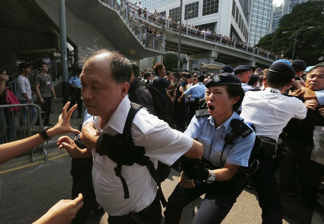 A policewoman tries to stop an anti-Occupy protester from breaking a police cordon to charge at pro-democracy protesters during a confrontation in Hong Kong October 13, 2014. Hundreds of unidentified people, some wearing masks, tried to break down protest barriers in the heart of Hong Kong's business district on Monday, scuffling with protesters who have occupied the streets for the past two weeks. (Photo by Bobby Yip/Reuters)