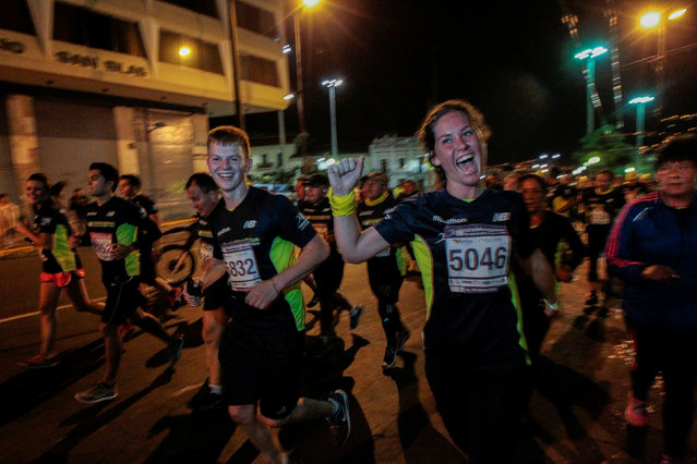 """U.S. citizens Ben Levey and Anna Casey gesture as they participate in the """"Churches route"""" night race in downtown Quito, Ecuador, August 27, 2016. (Photo by Guillermo Granja/Reuters)"""