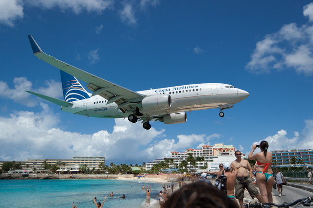"""""""Landing. In St Maarten, there is a named named Maho, directly across the street from Princess Juliana airport's landing strip. This gives adventurous beach-goers an unforgettable experience as planes come in. This particular plane is by no means the largest to land here"""". (Photo by Paul Brousseau)"""