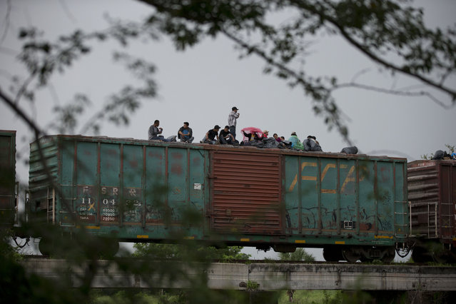 In this Friday, June 20, 2014 photo, Central American migrants wait atop the freight train they had been traveling north on, as it starts to rain after the train suffered a minor derailment outside Reforma de Pineda, Chiapas state, Mexico. (Photo by Rebecca Blackwell/AP Photo)