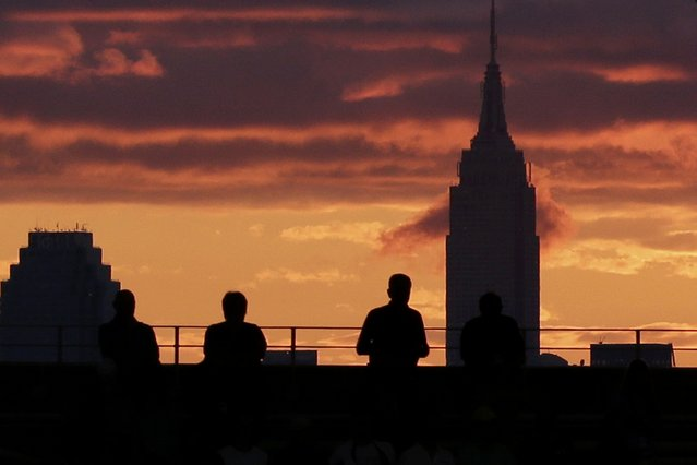 Fans watch the sunset and the Empire State Building (R) from Arthur Ashe Stadium ahead of the mens final between Roger Federer of Switzerland and Novak Djokovic of Serbia at the U.S. Open Championships tennis tournament in New York, September 13, 2015. (Photo by Lucas Jackson/Reuters)