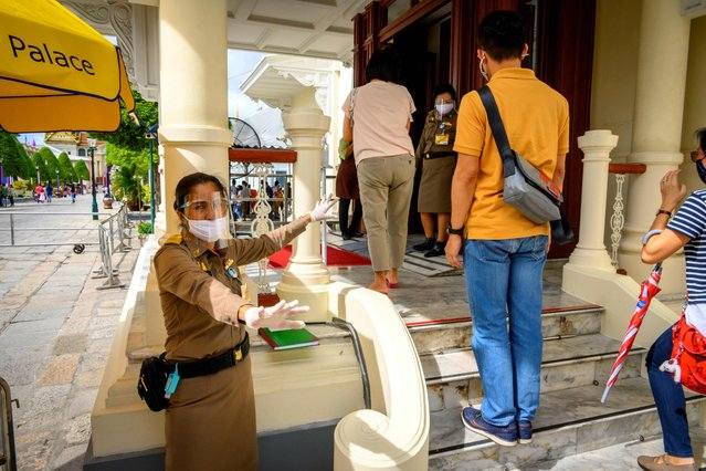 An officer enforces social distancing at the entrance of the Grand Palace in Bangkok on June 7, 2020, as it reopened for visitors following restrictions to halt the spread of the COVID-19 novel coronavirus. (Photo by Mladen Antonov/AFP Photo)