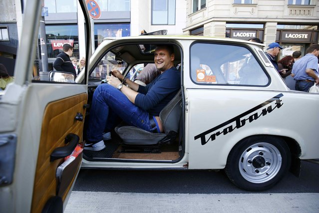 A man tries to get at the steering of a GDR-made Trabant car during the celebrations of the 25th anniversary since the reunification of East and West Germany, in Frankfurt, Germany, October 3, 2015. (Photo by Kai Pfaffenbach/Reuters)