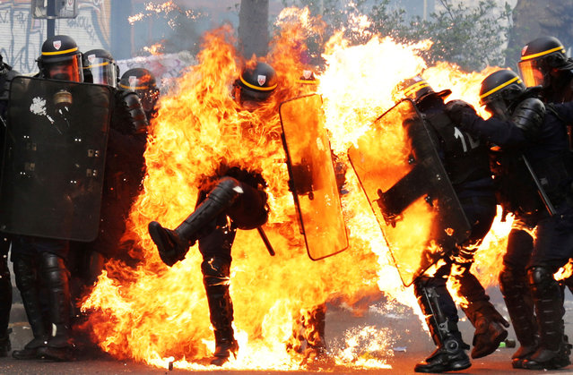 French CRS anti-riot police officers are engulfed in flames as they face protesters during a march for the annual May Day workers' rally in Paris on May 1, 2017. (Photo by Zakaria Abdelkafi/AFP Photo)
