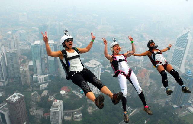 BASE jumpers leaps from the 300-metre high Kuala Lumpur Tower during the International Tower Jump in which more than 100 people take part, on a hazy day in Kuala Lumpur, Malaysia October 2, 2015. (Photo by SIPA Press/REX Shutterstock)