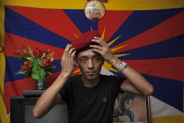 "In this Friday, June 6, 2014 photo, Exile Tibetan Dorjee Tashi adjust the beret he calls ""Che Guevera cap"" as he poses for a photograph in front of a flag of Tibet in his room in New Delhi, India. Tashi had just returned from a protest rally when he received news of his father's death in a voice message stored on his phone. His one wish was to meet his father again and considers this unfulfilled wish as part of his karma. (Photo by Tsering Topgyal/AP Photo)"