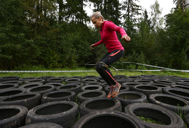 "A woman jumps with the legs tied by rope though old tires as she takes part in an extreme run ""Bison race"" near the town of Logoisk, Belarus September 17, 2016. (Photo by Vasily Fedosenko/Reuters)"