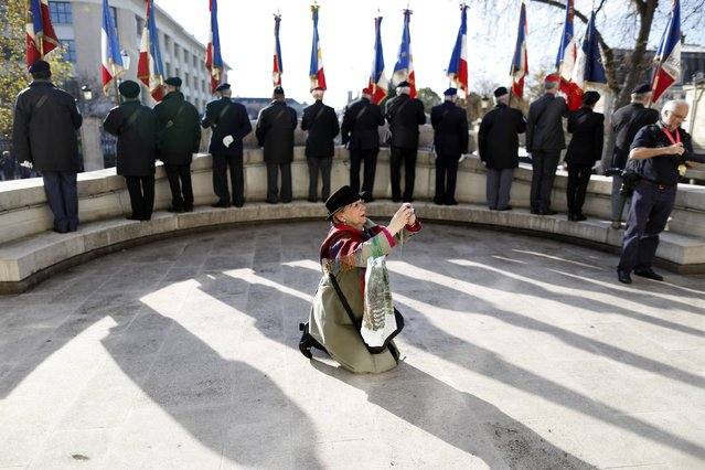 A spectator takes a picture in front of flag bearers at a war memorial during an Armistice Day ceremony to commemorate the end of World War One at Epernay, eastern France, November 11, 2014. (Photo by Charles Platiau/Reuters)