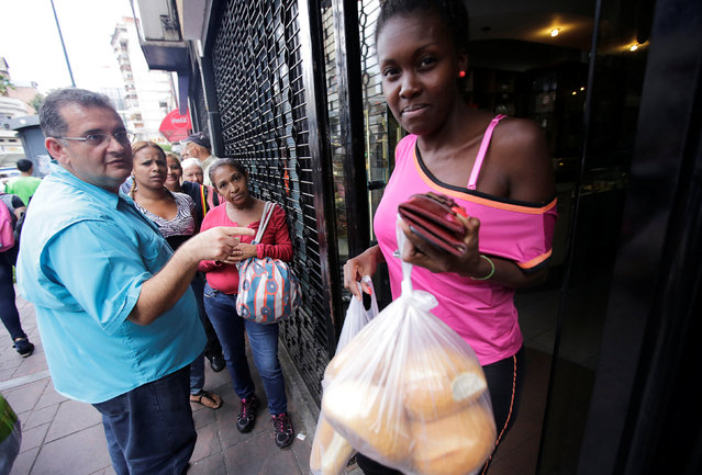 A woman leaves from a bakery after she buys fresh bread in Caracas, Venezuela September 15, 2016. (Photo by Henry Romero/Reuters)